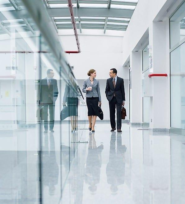 Mann und Frau gehen am Gang eines Buerogebaeudes